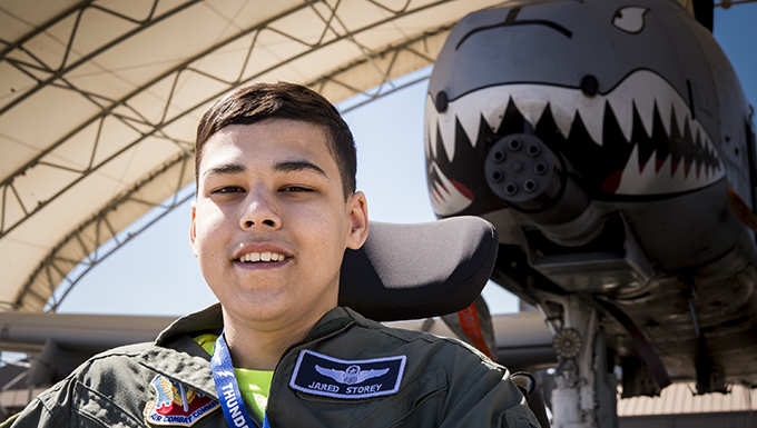 Jared Storey poses for a photo in front of an A-10C Thunderbolt II on the flightline, March 14, 2018, at Moody Air Force Base, Ga. Pilots from the 23d Fighter Group made Storey, who is terminally ill with Osteosarcoma, a rare form of bone cancer, an honorary A-10 pilot for a day. (U.S. Air Force photo by Andrea Jenkins)