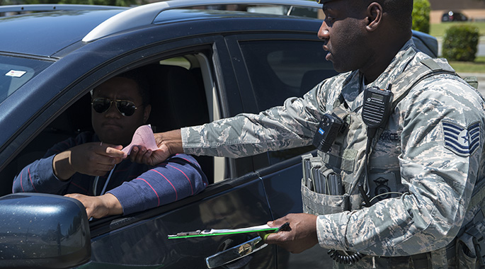 Tech. Sgt. Jamaal Smalls, 23d Security Forces Squadron (SFS) flight chief, hands a citation to Airman 1st Class Eugene Oliver, 23d Wing photojournalist apprentice, during a simulated distracted driving traffic stop to, April 17, 2018, at Moody Air Force Base, Ga. Since January 2018 there have been 13 distracted driving incidents at Moody, which has prompted the SFS patrolmen to heavily enforce distracted driver consequences for motorists on the installation. (U.S. Air Force photo by Senior Airman Janiqua P. Robinson)