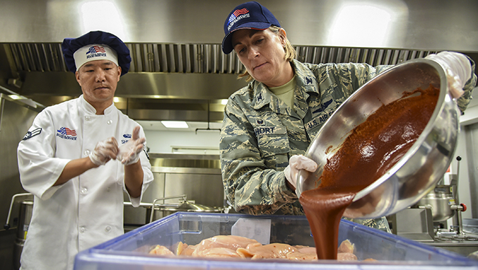Col. Jennifer Short, right, 23d Wing (WG) commander, pours sauce onto chicken during an immersion tour, June 11, 2018, at Moody Air Force Base, Ga. Short and Chief Master Sgt James Allen, 23d WG command chief, toured the Georgia Pines Dining Facility and the Information Learning Center to gain a better understanding of their overall mission, capabilities and comprehensive duties. (U.S. Air Force photo by Airman 1st Class Eugene Oliver)