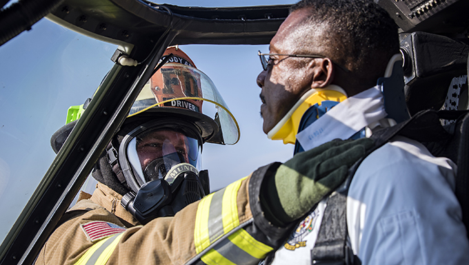 Senior Airman James Muncy, left, 23d Civil Engineer Squadron (CES) firefighter, applies a neck brace onto Charlie Johnson, 23d CES assistant fire chief, during an HH-60G Pave Hawk simulated rescue training scenario, June 20, 2018, at Moody Air Force Base, Ga. 23d CES firefighters conducted the training to evaluate their overall knowledge and preparation of how to properly shut down and rescue crew members from an HH-60. (U.S. Air Force photo by Airman 1st Class Eugene Oliver)
