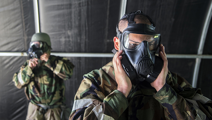 Airman 1st Class Phillip Pham, right, 23d Civil Engineer Squadron execution support specialist, performs a seal check on his gas mask during a Chemical, Biological, Radiological, Nuclear and Explosive (CBRNE) Olympics, June 21, 2018, at Moody Air Force Base, Ga. Moody held its first CBRNE Olympics to further Airmen's overall knowledge on all of the aspects of CBRNE through a new method that was meant to establish a sense of competition and camaraderie. (U.S. Air Force photo by Airman 1st Class Eugene Oliver)