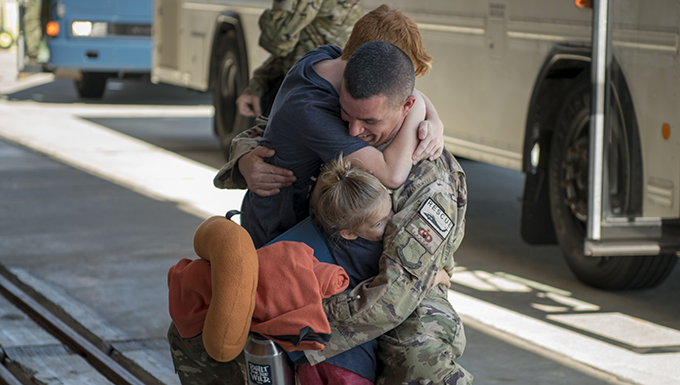 An Airman reunites with his family during the 41st Rescue Squadron's (RQS) redeployment ceremony, July 10, 2018, at Moody Air Force Base, Ga. While deployed, the 41st RQS and the 41st Helicopter Maintenance Unit provided combat search and rescue capabilities and maintenance operations in support of Combined Joint Task Force-Horn of Africa. (U.S. Air Force photo by Airman Taryn Butler)