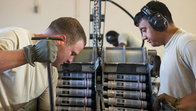 Tech. Sgt. Robert Lewis, left, 476th Maintenance Squadron (MXS) NCO in charge of line delivery, and Airman 1st Class Jordan Sili, 23d MXS crew member, feed munitions into ammo bins during a 30mm rounds processing, July 11, 2018, at Moody Air Force Base, Ga. This total force integration training with the 23d and 476th MXS allowed Airmen to work together to identify more ways to efficiently and safely conduct their mission. The munitions flight ensures the A-10C Thunderbolt IIs are armed with 30mm rounds to make sure they are able to continue their mission while at home station and deployed. (U.S. Air Force photo by Airman 1st Class Erick Requadt)